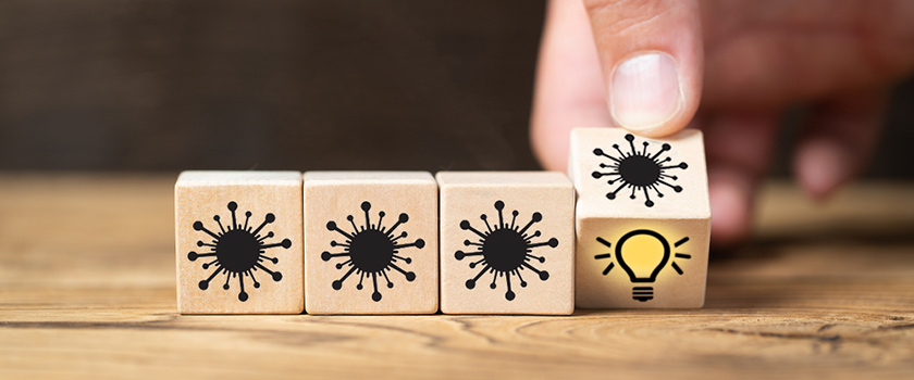 Wooden dice featuring images of virus and lightbulb